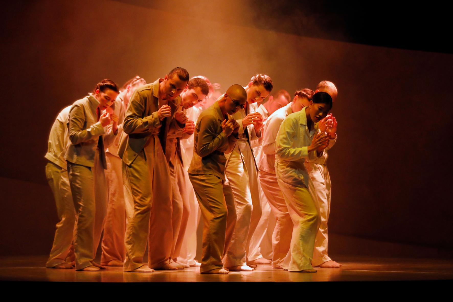 Een groep dansers met handen als vuisten voor de borst, ietwat gebogen en ingetogen dansend in een oranje licht.