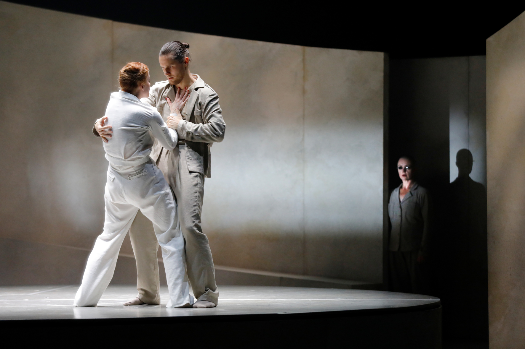 Two dansers in duet on the stage. We see the back of a female, who has her hand against the chest of her partner. He has his hand around her wrist and the other arm on her back. A mysterious figure is watching in the background.