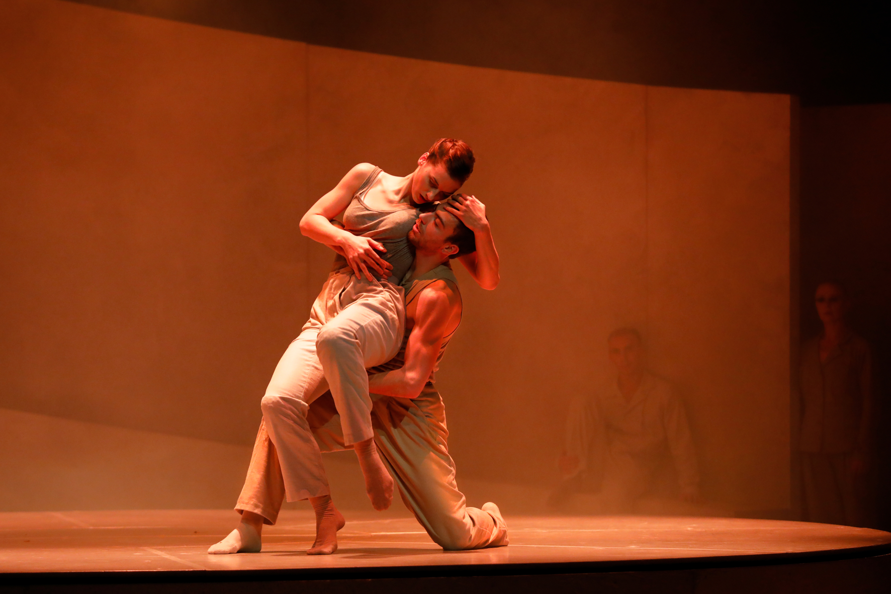 A male and female dancer in a light suit on a stage in orange lights. He is on one knee and she leans on him and has his head in her hands.
