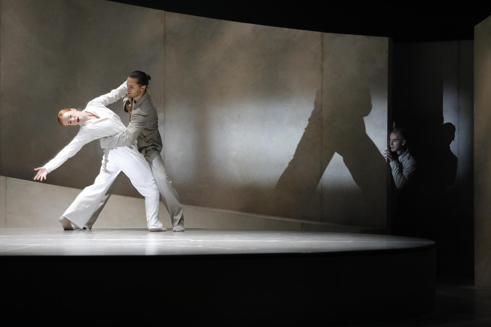 Twee dansers op het podium. De mannelijke danser heeft zijn arm om haar rug geslagen en zij leunt naar achteren en strekt haar arm uit naar achter. Op de achtergrond kijkt iemand toe in de schaduw.