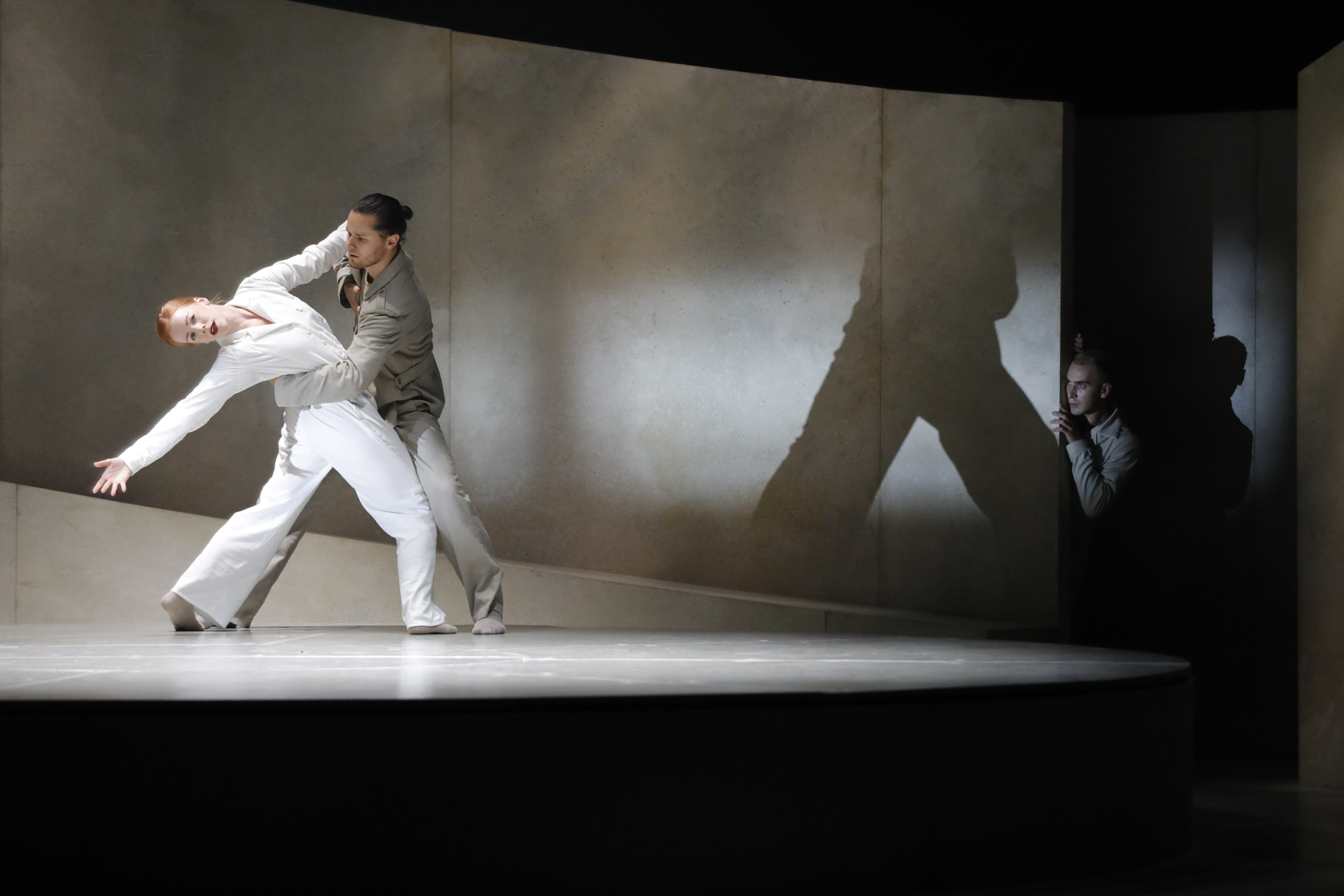 Two dancers on stage. The male dancer has his arm around her back as she leans backwards and had her arm stretched back. At the background someone is watching from the shadow.