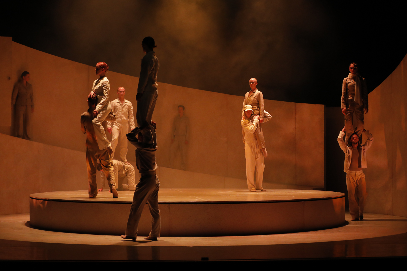 A group of dansers on a round stage in orange lighting with smoke. A few of them standing on eachothers shoulders.