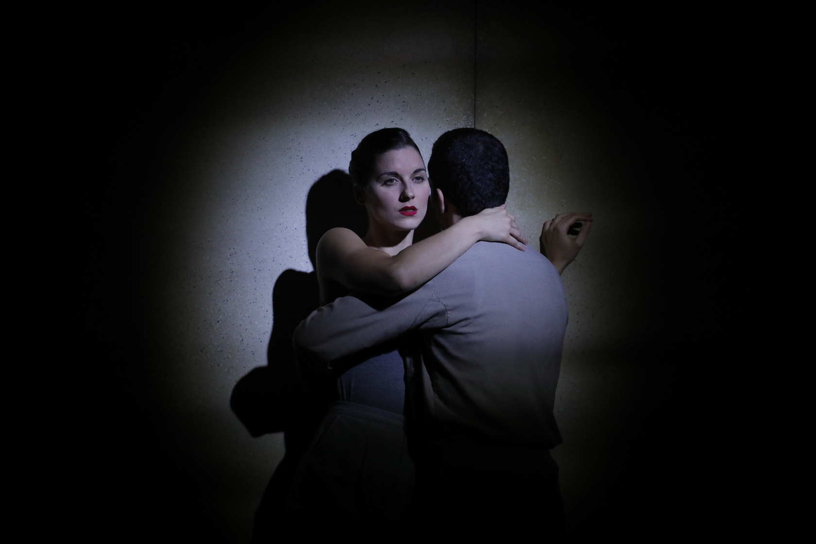 Male and female in a firm hug against a wall. We see her sad face, he has his back turned to the audience.