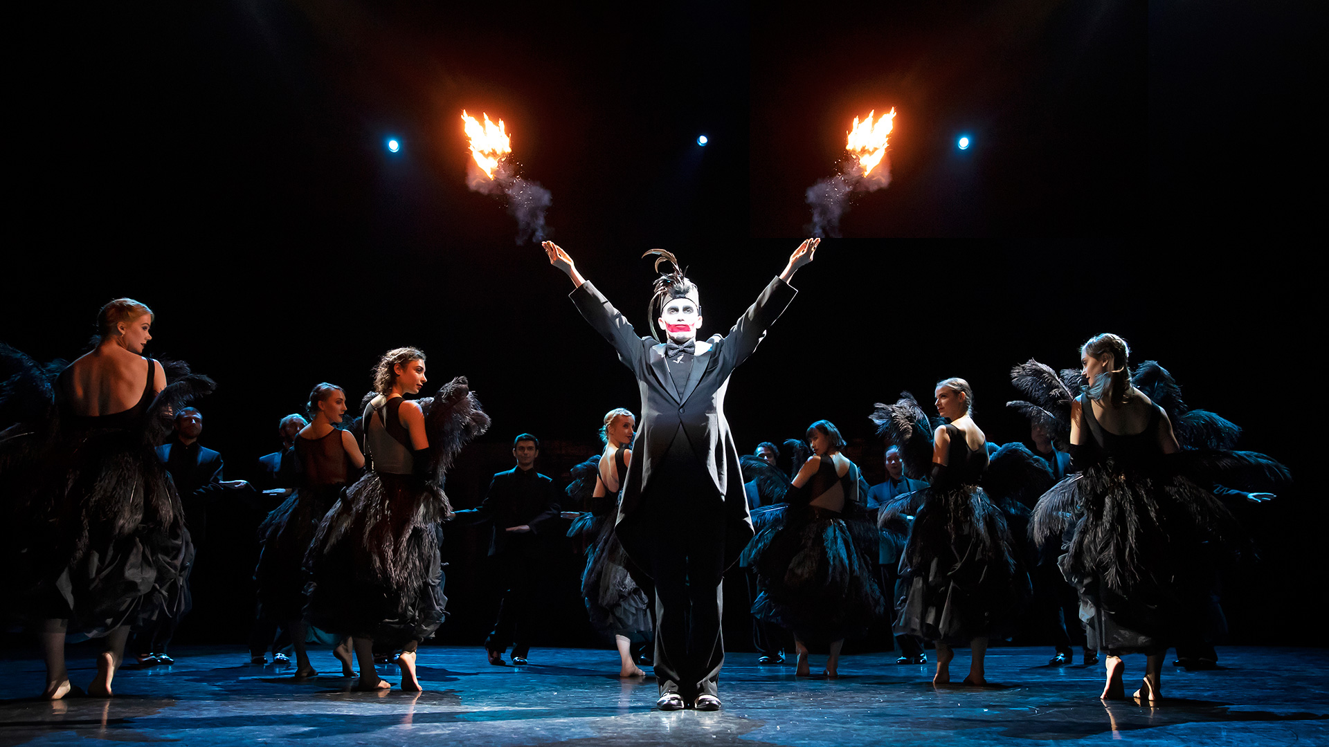 A magician shoots flames in the sky, while the ensemble dances in the background in The Great Bean by Scapino Ballet Rotterdam