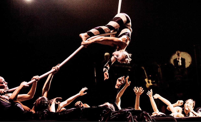 Een danseres die op haar kop aan linten hangt met handen van anderen die naar haar reiken