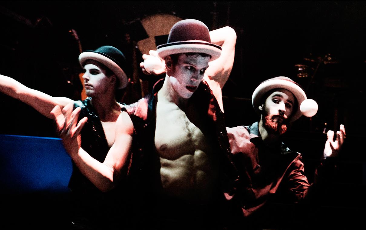 Drie dansers met bolhoeden op en jongleerballen in de handen