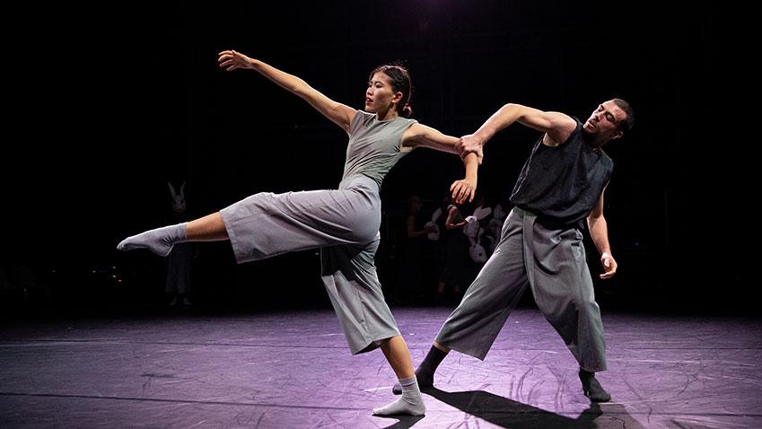 Vrouwelijke danser strekt haar been voor zich uit, mannelijke danser trekt haar terug aan haar linkerarm