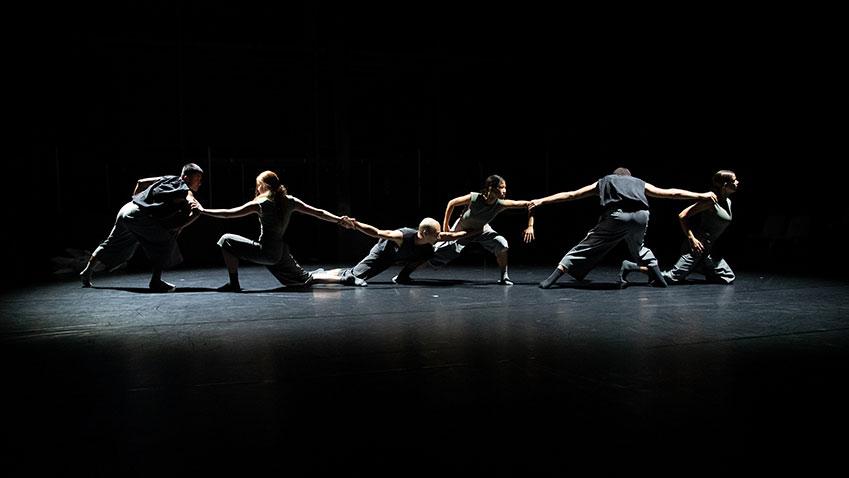 Zes dansers gekleed in het grijs, die elkaar vasthouden met de armen