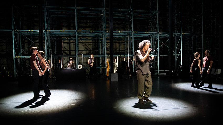 DOX in het midden in een spotlight, met links en rechts dan hem elk twee dansers die ook in spotlichten staan