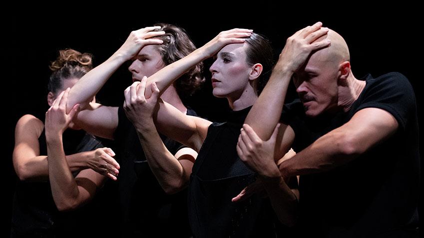 Drie dansers met hand tegen het voorhoofd, met de andere armen en handen aan elkaar verbonden
