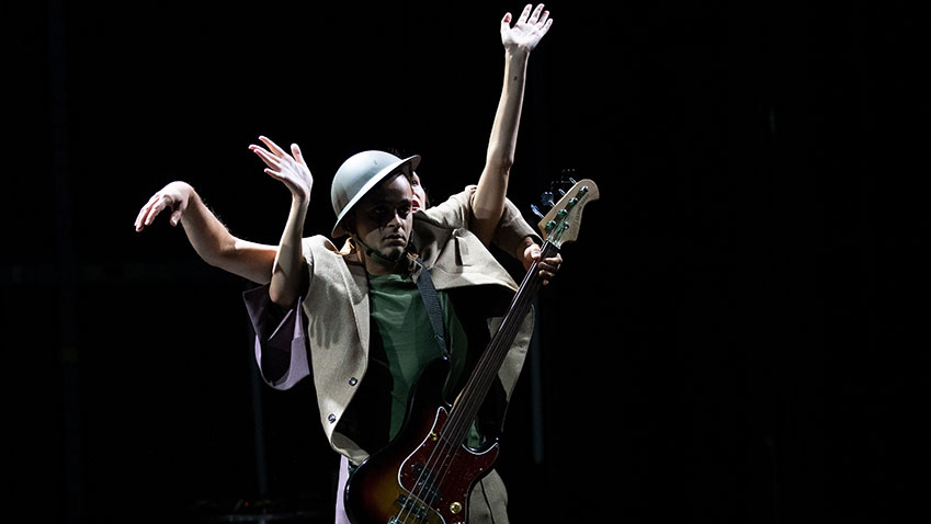 Mannelijke danser met helm en giraar met achter hem een vrouwelijke danser die haar handen om hoog houdt
