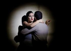 Man en vrouw in omhelzing tegen een muur. Je ziet haar verdrietige gezicht, hij staat met de rug naar het publiek toegekeerd.
