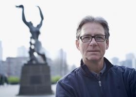 Portretfoto van Ed Wubbe buiten met op de achtergrond de binnenhaven van Rotterdam en het beeld De Verwoeste Stad van Zadkine