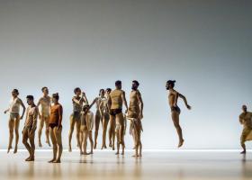Foto uit de voorstelling Henry van Itamar Serussi met dansers die in een groep, op de plaats afzonderlijk van elkaar springen