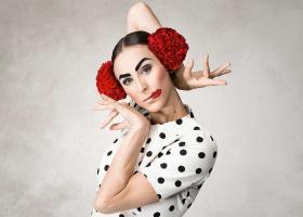 Beeld van danseres Maya voor de voorstelling Pablo, met een wit shirt met zwarte stippen, grote rode bloemen in het haar en rode lippen schuin op haar mond gestift