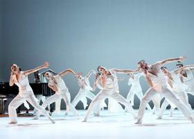 Beeld uit Pas de Deux met dansers in het wit en op de achtergrond een vleugel met daaraan Michiel Borstlap - foto Hans Gerritsen