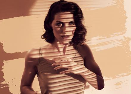 Zachtbruine foto van een vrouw met donker halflang haar die ons met grote ogen aankijkt. Ze draagt een hemdje en heeft haar hand voor haar borst. Schaduw van lamellen valt over haar heen.