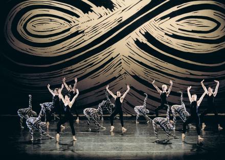 Ensemble van dansers op het podium met op de achtergrond een zwart met beige grafische print