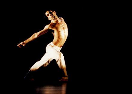 Beeld van een danser in witte broek met ontbloot bovenlijf uit Le Sacre du Printemps - Choreografie Ed Wubbe