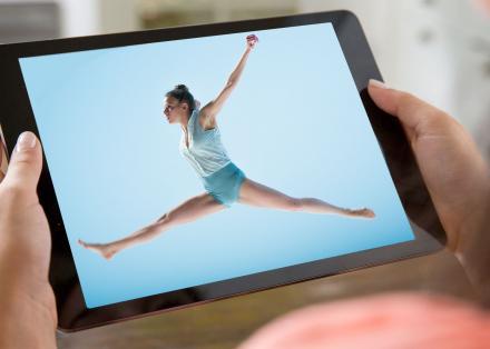 Danseres op blauwe achtergrond doet een sprong, en wordt bekeken op een tablet