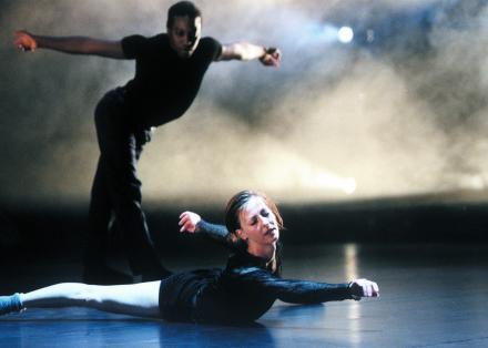 Twee dansers, een staand en een liggend op de vloer uit Single Manouvres - Choreografie Ed Wubbe