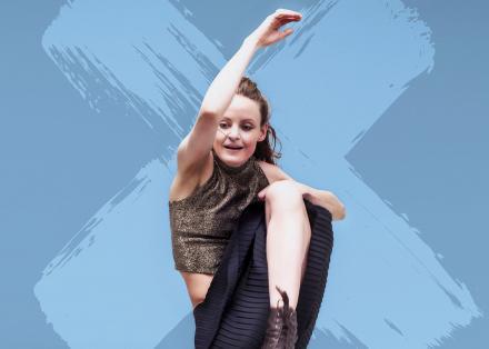 Danseres op een blauwe achtergrond met geverfd diagonaal kruis. Zij draagt een gouden glittertop en heeft haar rechterarm opgeheven en linkerknie volledig omhoog tot haar borst.