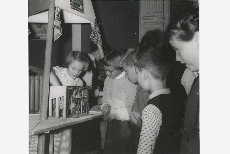 Kinderen bij het jubileumboek met voorstellingsmaquette (fotograaf onbekend)